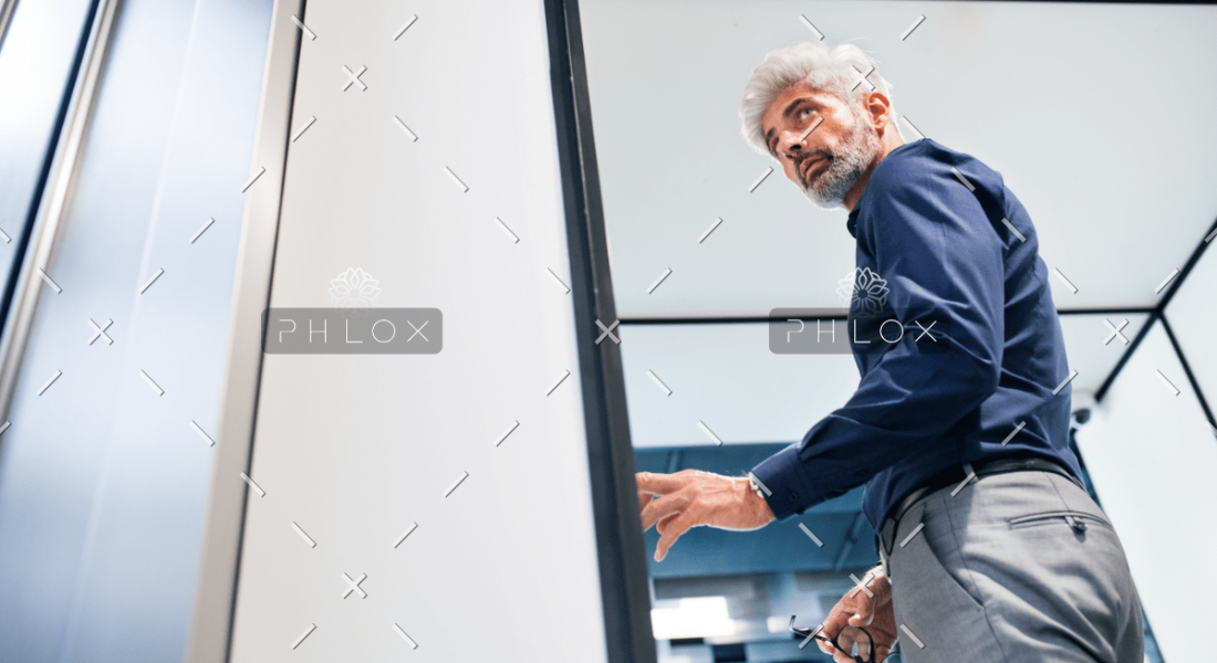 demo-attachment-914-mature-businessman-in-the-office-standing-P4MENHG